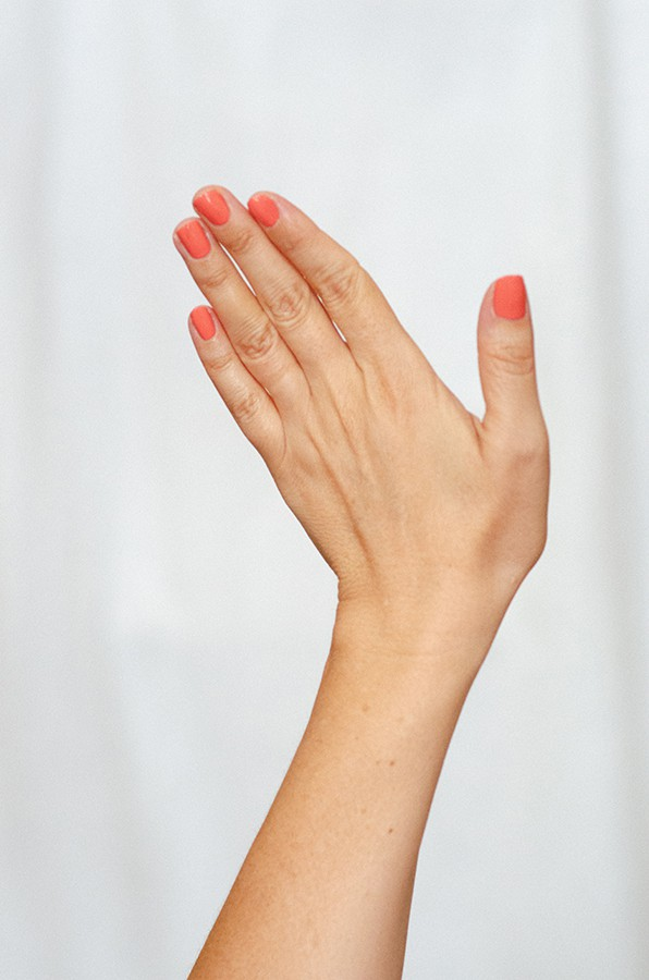 Coral pink nail polish hand swatch on fair skin tone by sienna