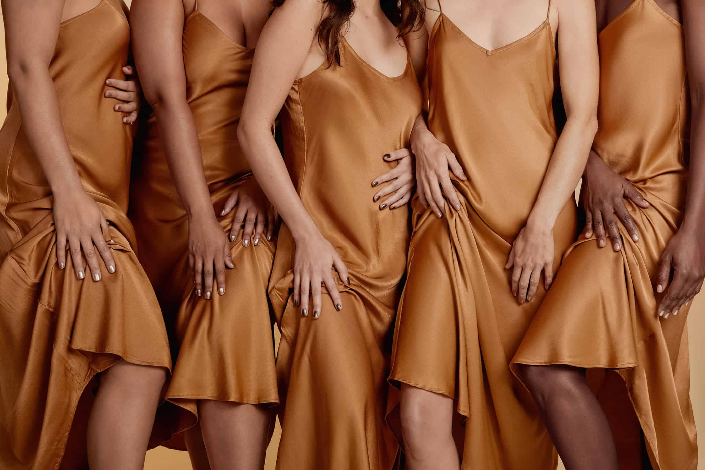 different skin tone models wearing the same silk gold dress and wearing crushed crystal nail polish by sienna