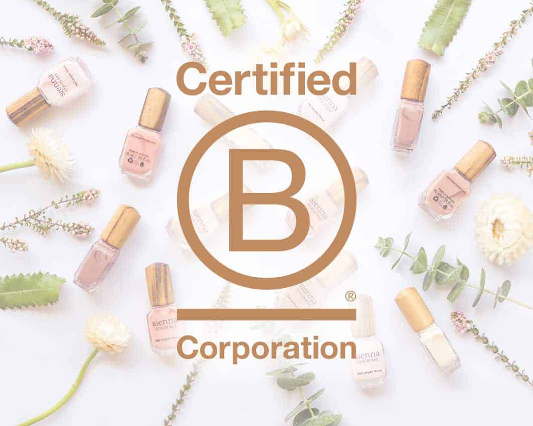 B-Corp logo over pink nail polish bottles with timber cap by sienna and white and pink flowers