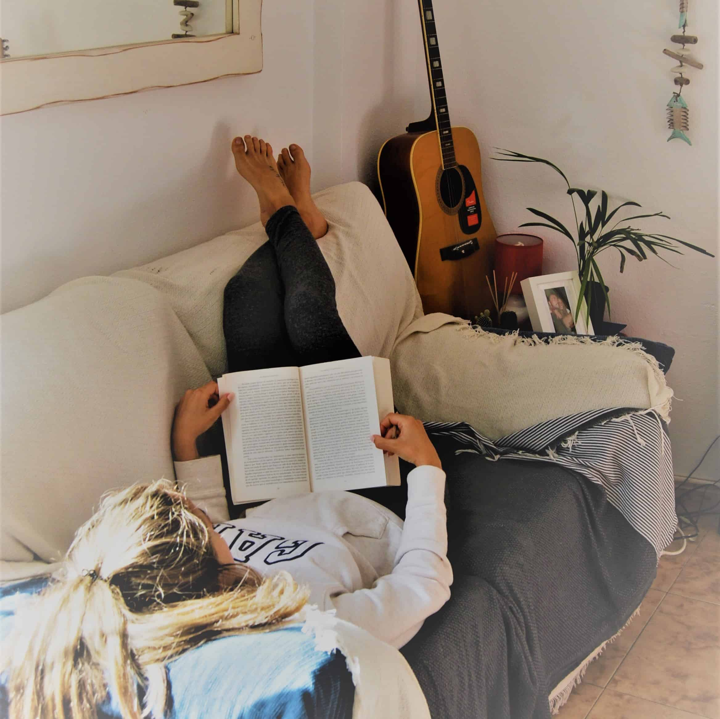 girl reading on her couch with her feet up in the air