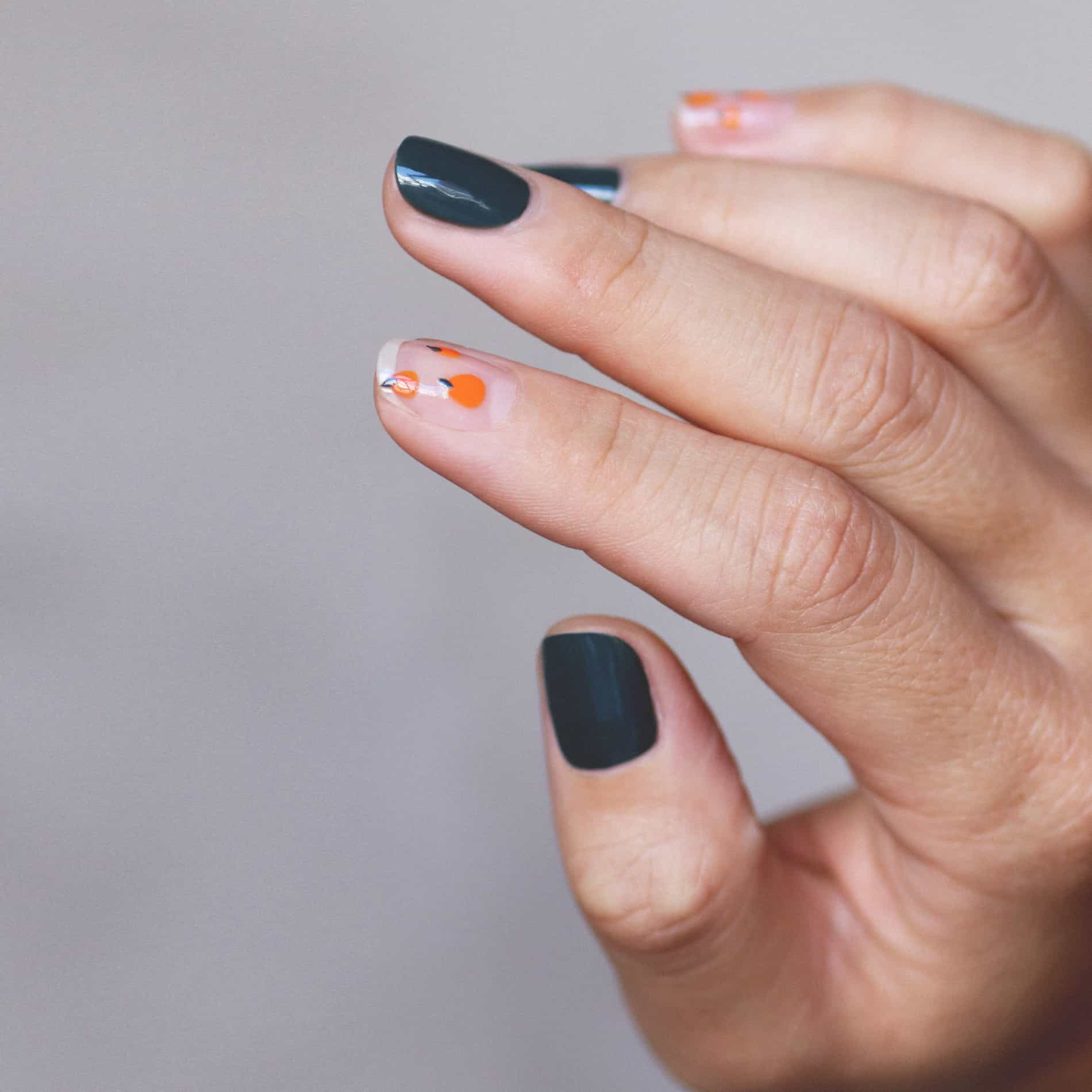 green and orange nail art hand swatch on fair skin tone by line spa and polish and sienna