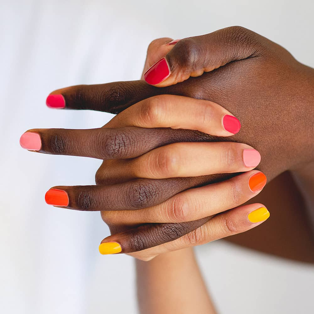 Ombre nail art with orange yellow pink and red nail polish on dark and medium skin tone by sienna