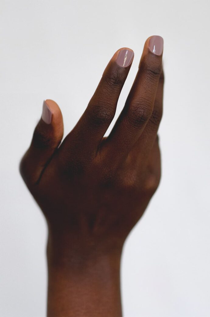 Mauve nail polish on dark skin tone