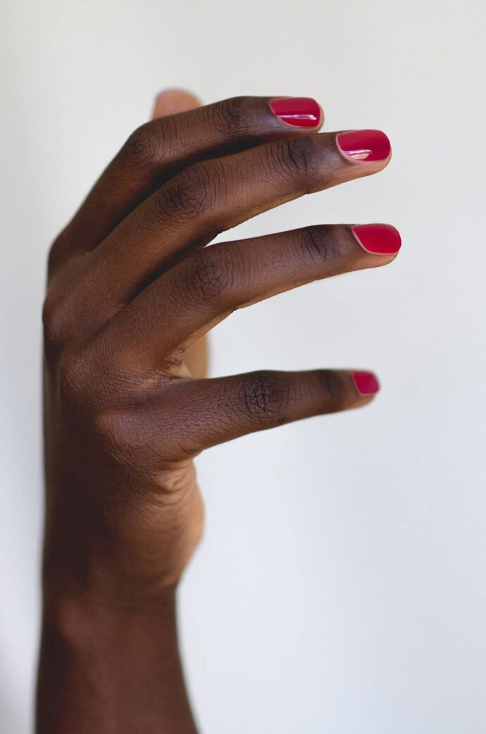plum nail polish on dark skin tone
