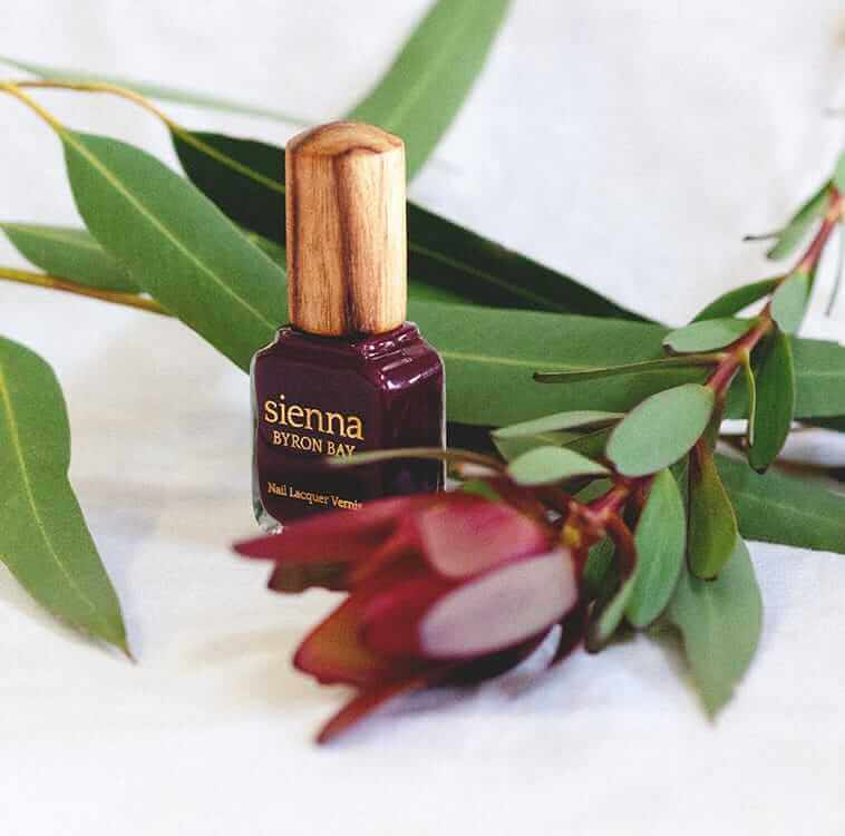 Magenta plum red nail polish glass bottle with timber cap in the middle of red flowers by sienna