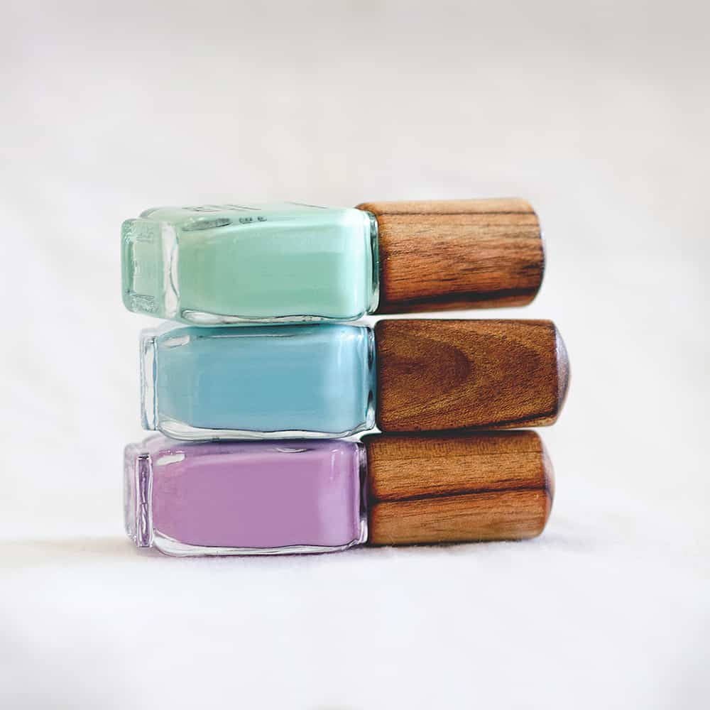 stack of three green blue and purple nail polish glass bottle with timber cap by sienna