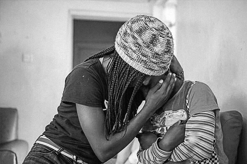 black and white photo of two kenyan teenage girls hugging