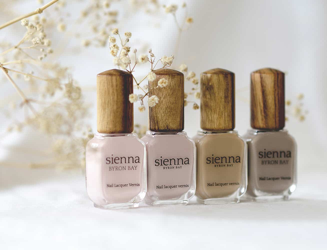 neutral nail polish glass bottle with timber cap by sienna and baby's breath flower in the background