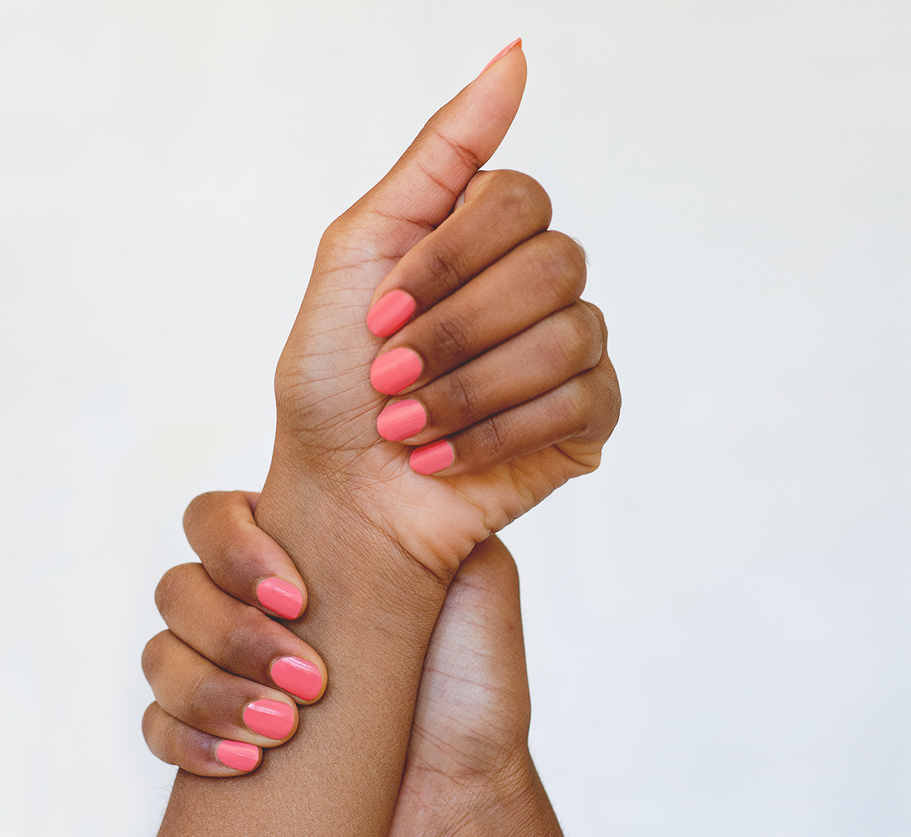 Peachy pink nail polish hand swatch on medium skin tone by sienna