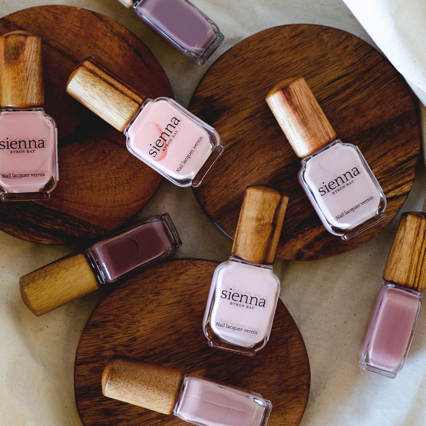 Top shot of neutral and purple nail polish glass bottles with timber cap by sienna