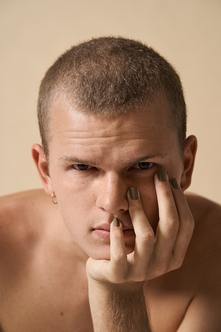 young man wearing green nail polish by sienna and resting his head on his hand