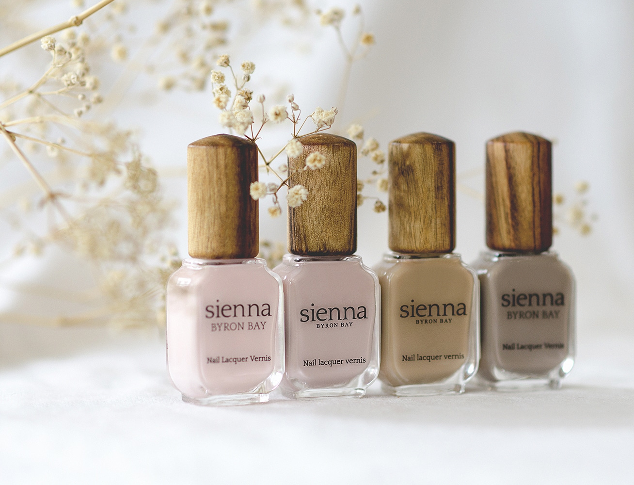 4 neutral nail polish bottles with timber cap by sienna with baby breath in the background